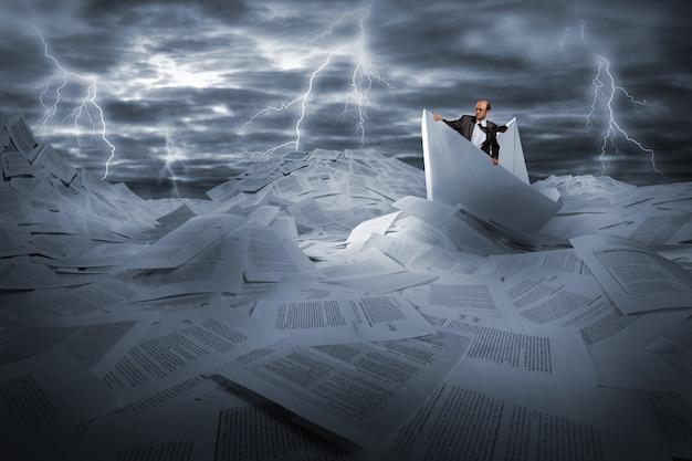 Zakenman zeilen in stormachtige papieren zee