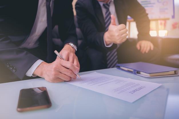 Zakenman zet handtekening op contract tijdens zakelijke bijeenkomst en geeft geld door na onderhandelingen met zakenpartners