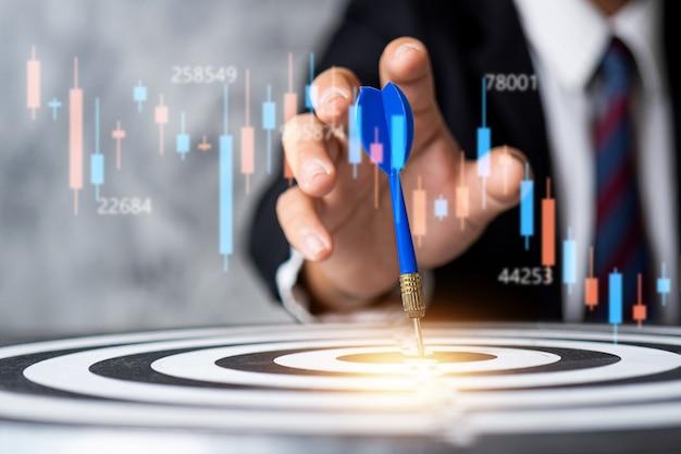 Zakenman zetten doel op dartbord, aandelenmarkt en financieel concept