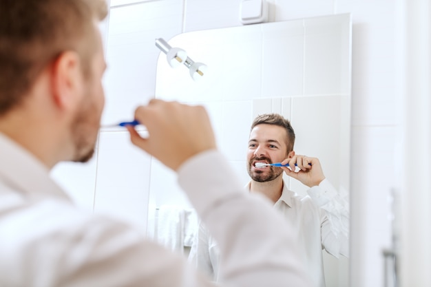 Zakenman zijn tanden poetsen terwijl hij voor spiegel in de badkamer staat.