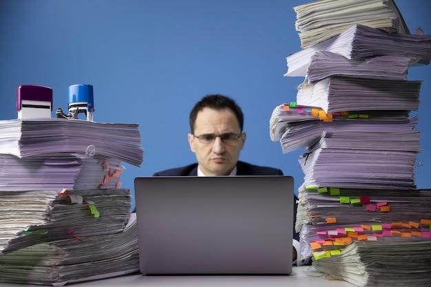 Zakenman zit aan bureau met enorme stapel documenten