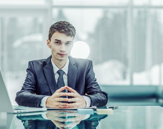 Zakenman zit aan een bureau voor een opengeklapte laptop. de foto heeft een lege ruimte voor uw tekst