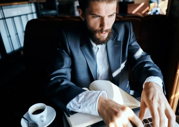 Zakenman zit in een café voor een laptop met een kopje koffie werk technologie levensstijl.