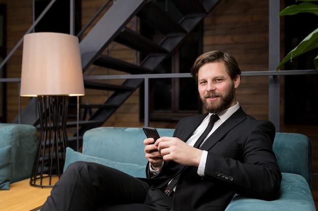 Zakenman zit in een stijlvol restaurant in een pak ontspannen en gebruikt de telefoon om te communiceren