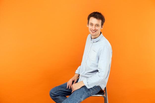 Zakenman zit op stoel kijkend naar camera en brede glimlach