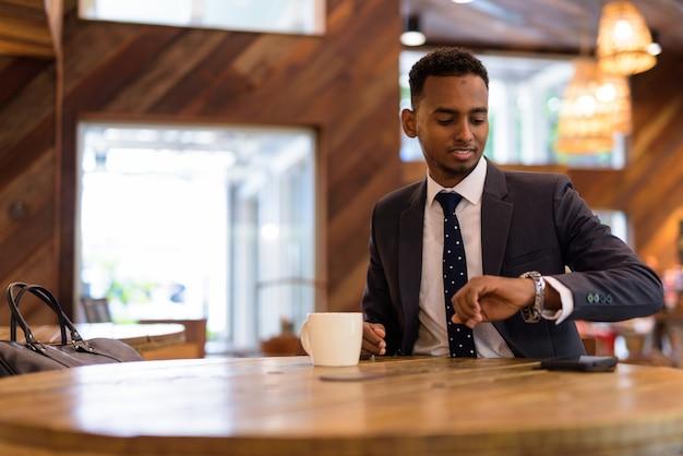 Zakenman zitten en het controleren van de tijd van zijn horloge in de coffeeshop