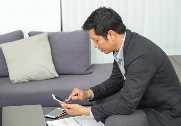 Zakenman zittend aan een bank en kijkt neer op mobiele telefoon