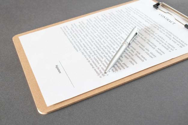 Zakenman zittend aan een bureau een contract ondertekenen met ondiepe focus op handtekening.