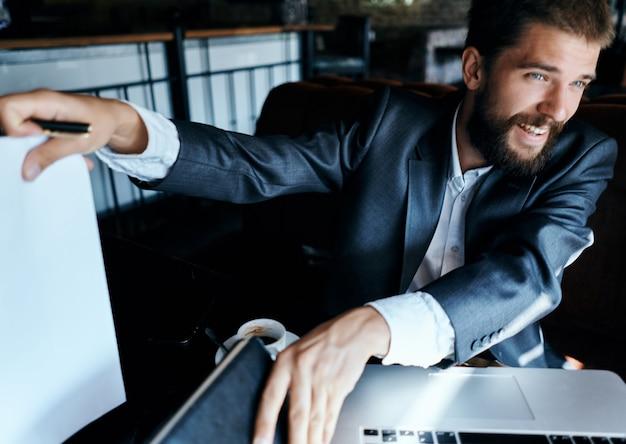 Zakenman zittend aan een tafel in een café papieren laptop werk