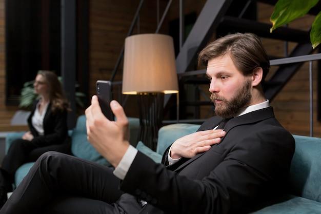 Zakenman zittend in een stijlvol restaurant in een pak ontspannen en gebruikt de telefoon om te communiceren