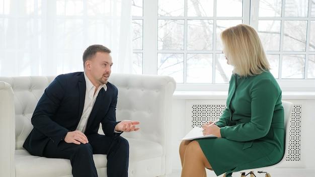 Zakenman zittend op de bank praten met vrouwelijke psycholoog