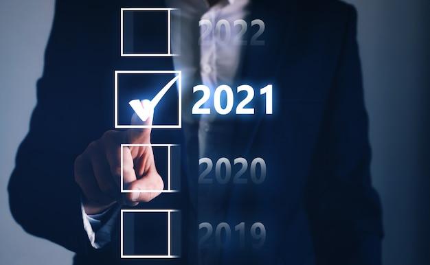Zakenmanhand aanraken en wijzen op 2021 jaar van de vier opties. bedrijfsplanning en gelukkig nieuwjaar concept. doelwit