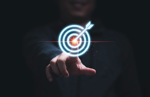 Zakenmanhand aanraken om dartbord te targeten voor opzet en prestatiedoelstellingen voor bedrijfsinvesteringsconcept.
