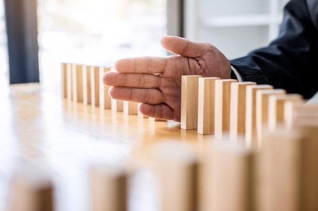 Zakenmanhand die dalend houten dominosteneneffect tegenhouden