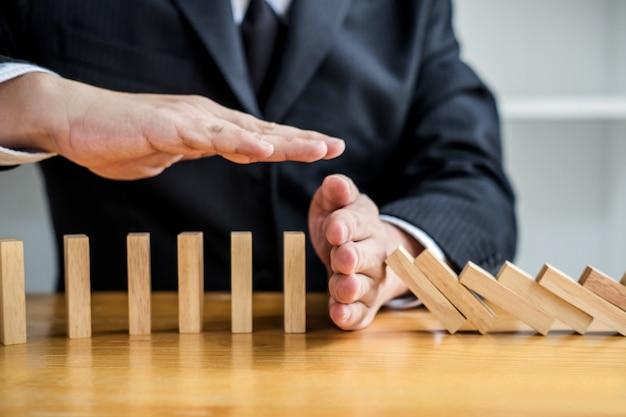 Zakenmanhand die dalend houten dominosteneneffect van ononderbroken omvergeworpen of risico tegenhouden