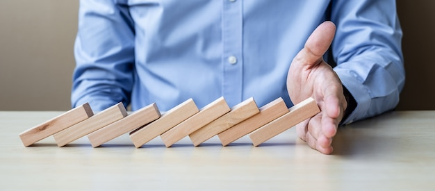 Zakenmanhand die dalende houten blokken of domino's tegenhouden