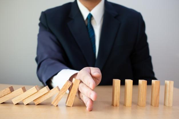 Zakenmanhand die dalende houten domino's stoppen. bedrijfsconcept van de bedrijfsrisicobeheersing. bedrijfsrisicoplanning en strategie.
