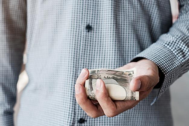 Zakenmanhand die de japanse stapel van het yenbankbiljet houden. zaken, geld, investeringen, financiën en betalingsconcepten