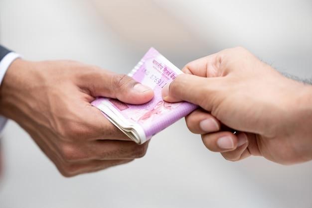 Zakenmanhand die de munt van geld indische roepie geven aan zijn partner