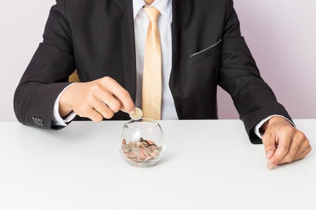 Zakenmanhand die de muntstukken op het glas zetten
