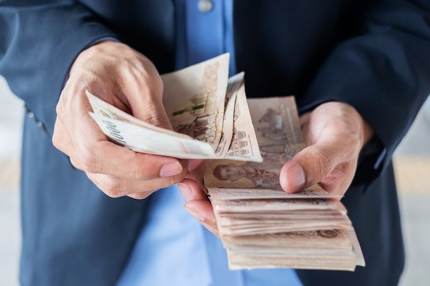 Zakenmanhand die de thaise stapel van het bahtbankbiljet houden.