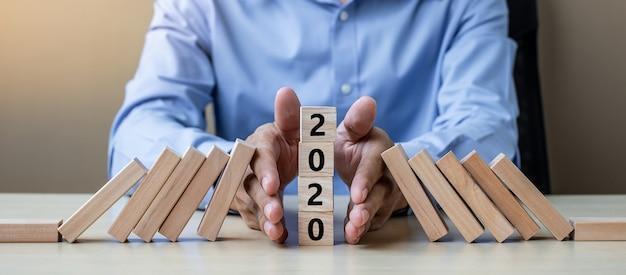 Zakenmanhand die het vallen van de houten blokken van 2020 tegenhouden.
