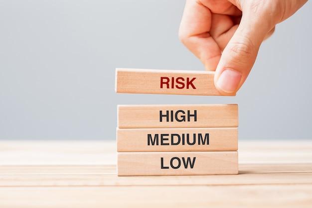 Zakenmanhand die houten blok met risicotekst plaatsen of trekken over high medium en low. planning, risicobeheer, economie, financiën en bedrijfsconcepten
