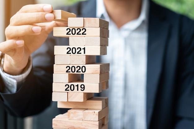 Zakenmanhand die houten blok op de toren plaatsen of trekken. risicobeheer, resolutie, strategie, oplossing, doel, zakelijke en nieuwjaarsvakantieconcepten