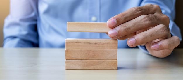 Zakenmanhand die houten bouwstenen houden