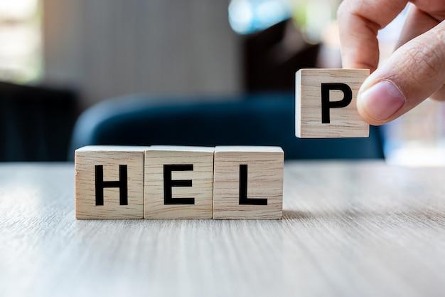 Zakenmanhand die houten kubusblok met help-bedrijfswoord houden. hulp, hoop, succesvol, bedrijfs en groepswerkconcept