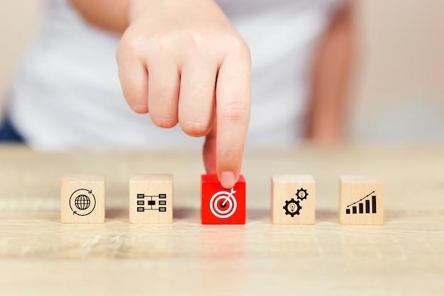 Zakenmanhand die houten kubusblok op bovenkant met het concept van het doelsucces zetten.