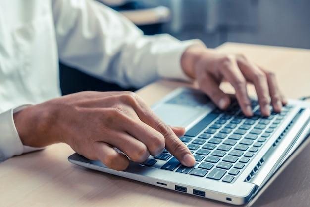Zakenmanhand die laptop computer in bureau met behulp van.