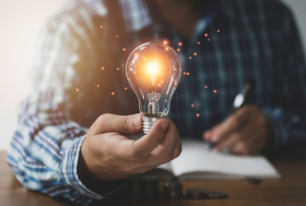 Zakenmanhand die lightbulb met het oranje gloeien en verbindingslijn houden. creatief denken idee concept.