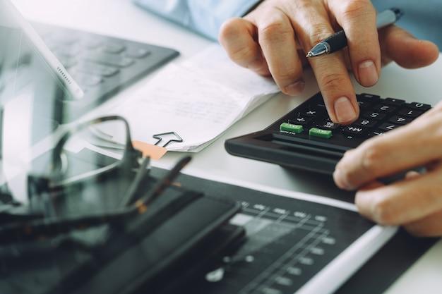 Zakenmanhand die met financiën over kosten en calculator en laptop met mobiele telefoon werken