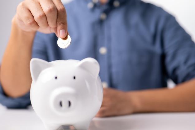 Zakenmanhand die muntstuk in spaarvarken zet geldbesparingsconcept bedrijfsfinanciën en investeringen