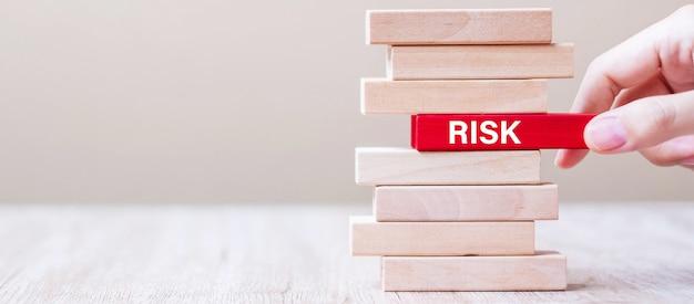 Zakenmanhand die of houten blok met risico-woord op de toren plaatsen trekken. bedrijfsplanning, management, oplossing, kansen en strategieconcepten