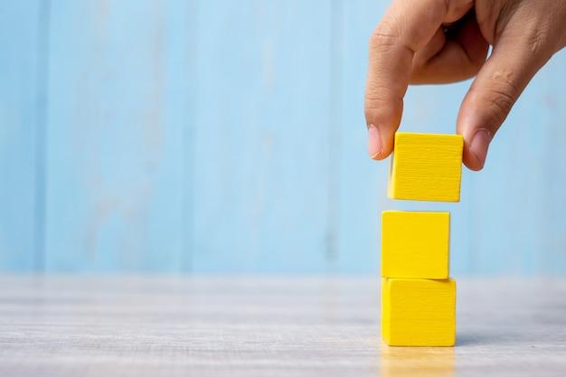 Zakenmanhand die of houten blok plaatsen trekken op het gebouw. bedrijfsplanning, risicobeheer, oplossing, strategie, anders en uniek