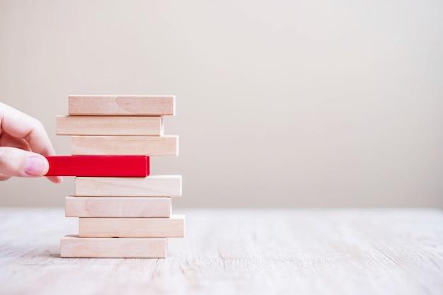 Zakenmanhand die of rood houten blok op de toren plaatsen trekken. bedrijfsplanning, risicobeheer, oplossing, oplossen en strategieconcepten