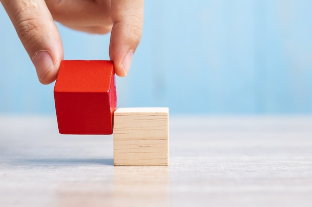 Zakenmanhand die of rood houten blok op het gebouw plaatsen trekken.