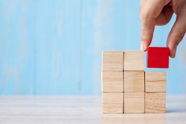 Zakenmanhand die of rood houten blok op het gebouw plaatsen trekken