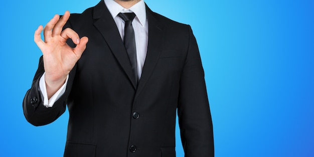 Zakenmanhand die ok / gelijkaardig die teken gesturing op gekleurde achtergrond wordt geïsoleerd