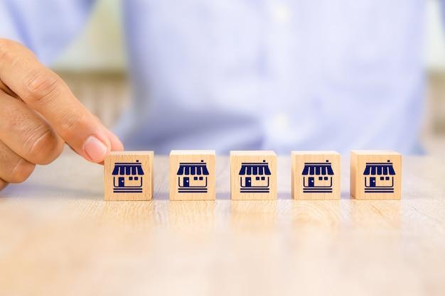 Zakenmanhand kiest houten blogplaats in lijn met franchise marketing iconen winkel.