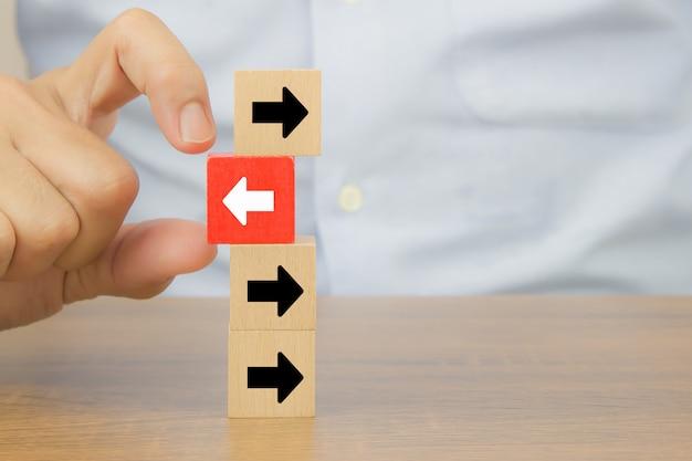 Zakenmanhand kiest kubus houten speelgoed blog met pijlpuntpictogrammen die naar tegengestelde richtingen voor zakelijke verandering wijzen.