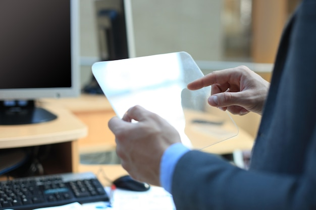 Zakenmanhand met transparante tablet en pc-computer.