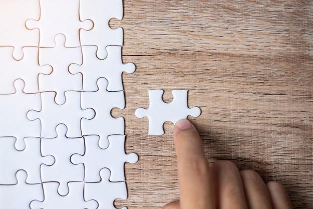 Zakenmanhand verbindend raadselstuk. bedrijfsoplossingen, missiedoelstelling, succesvol, doelen, samenwerking, partnerschap en strategie