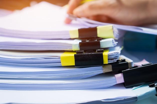 Zakenmanhanden die in stapels document dossiers werken voor het zoeken van controlerend onvolledig document