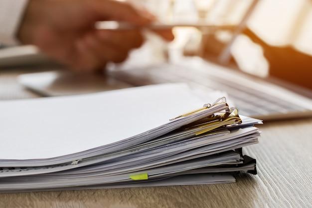 Zakenmanhanden die pen houden voor het werken in stapels van document dossiers
