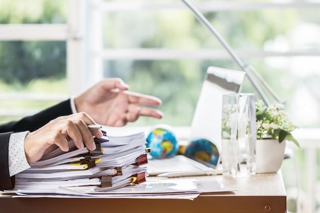 Zakenmanhanden die pen voor het werken in stapels van document dossiers houden die informatiezaken zoeken