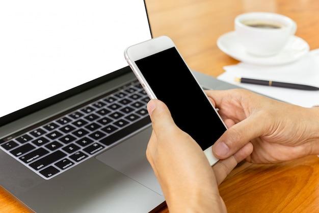 Zakenmanhanden die slimme telefoon over laptop met behulp van bij bureau
