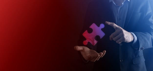 Zakenmanhanden verbindende puzzelstukjes die de samenvoeging van twee bedrijven of een joint venture, partnerschap, fusies en overnameconcept vertegenwoordigen.